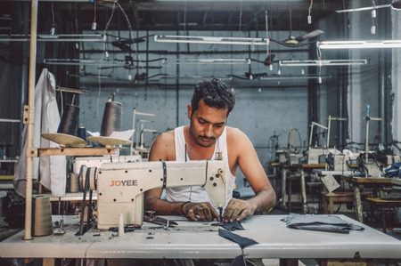 stitching machine: MUMBAI, INDIA - 12 JANUARY 2015: Indian worker sews in clothing factory in Dharavi slum. Post-processed with grain, texture and colour effect.