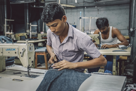 india: MUMBAI, INDIA - 12 JANUARY 2015: Indian workers sew in clothing factory in Dharavi slum. Post-processed with grain, texture and colour effect.