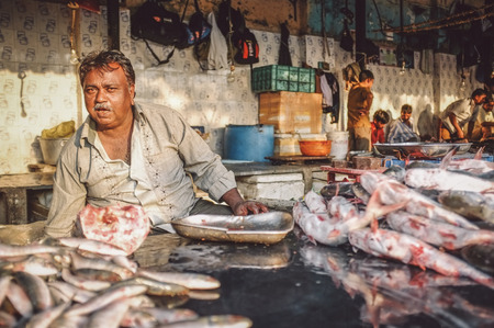 dhobi ghat: MUMBAI, INDIA - 08 JANUARY 2015: Worker on a fishmarket posing while waiting for customers. Post-processed with grain, texture and colour effect. Editorial