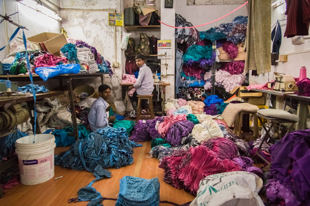 MUMBAI, INDIA - 12 JANUARY 2015: Two men work in small underwear factory in Dharavi slum. Dharavi is one of the largest slums in the world.