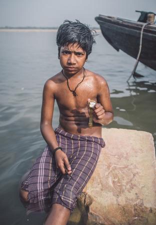 niño sin camisa: VARANASI, INDIA - 25 DE FEBRERO DE 2015: El muchacho indio se sienta sin camisa en la roca en el río Ganges y que miran las que encontró. Post-procesado con el grano, la textura y el efecto de color. Editorial