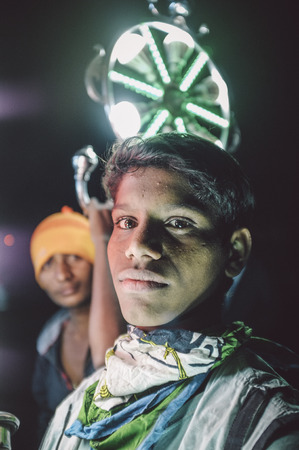 bridegrooms: JODHPUR, INDIA - 08 FEBRUARY 2015: Young Indian boys work as light holders in bride-grooms wedding procession. Post-processed with grain, texture and colour effect.