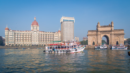 MUMBAI, INDIA - 17 JANUARY 2015: The Gateway of India is a monument built during the British Raj in Mumbai. Taj Mahal Palace Hotel is a five-star hotel located in the Colaba region of Mumbai.