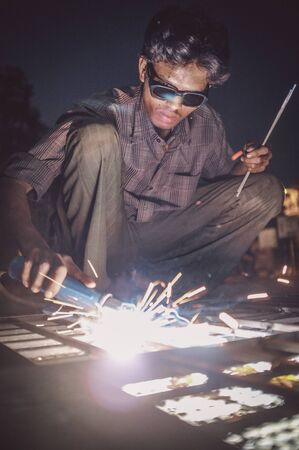 welds: KAMALAPURAM, INDIA - 02 FABRUARY 2015: Indian worker welds heavy metal parts on street in dusk. Post-processed with grain, texture and colour effect. Stock Photo