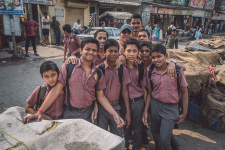 schoolboys: MUMBAI, INDIA - 16 JANUARY 2015: Schoolboys dressed in uniform gather around for a photograph in slum street. Post-processed with grain, texture and colour effect.