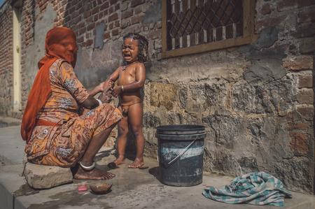 GODWAR REGION, INDIEN - 15. FEBRUAR 2015: Indische Mutter sitzt und wäscht nackten Jungen. Frau hat Gesicht mit Kopftuch bedeckt. Nachbearbeitet mit Maserung, Textur und Farbeffekt.