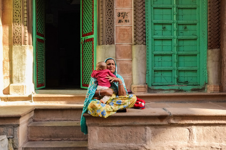 sari: JODHPUR, INDIA - 07 FEBRUARY 2015: Grandmother in colorful sari sitting in front of home holding grandchild. Stock Photo