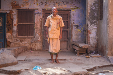 bindi: VARANASI, INDIA - 21 FEBRUARY 2015: Pilgrim dressed in lungi, shirt and scarf with paint on face stands in street next to old house.