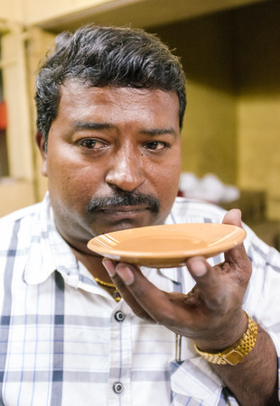 cool down: MUMBAI, INDIA - 05 FEBRUARY 2015: Portrait of Indian man drinking milk tea in traditional style. Drinking hot tea from saucer makes it possible for tea to cool down quicker. Editorial