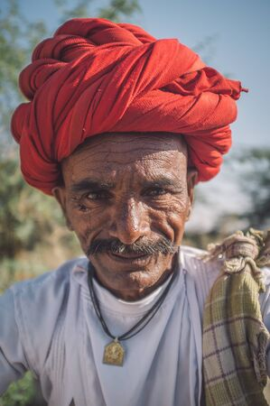 gujarat: GODWAR REGION, INDIA - 14 FEBRUARY 2015: Elderly Rabari tribesman with red turban. Post-processed with grain, texture and colour effect. Stock Photo