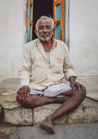 cross processed: KAMALAPURAM, INDIA - 02 FABRUARY 2015: Indian elderly man sits in front of his home. Post-processed with grain, texture and colour effect.
