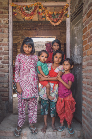 six girls: GODWAR REGION, INDIA - 15 FEBRUARY 2015: Six girls from same family stand in doorway under decorated door arch. Post-processed with grain, texture and colour effect.