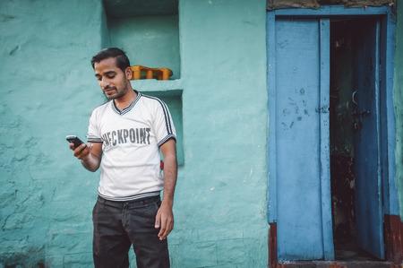viso di uomo: Kamalapuram, INDIA - 02 FABRUARY 2015: uomo indiano guarda al suo telefono cellulare fuori dalla sua casa. Post-elaborazione con il grano, la consistenza e l'effetto del colore.