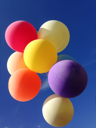 helium: Colourful balloons filled with helium floating on blue sky background Stock Photo