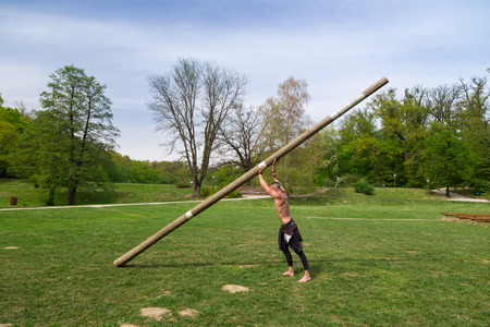 balk: Young athlete man training in the park with huge wooden log.
