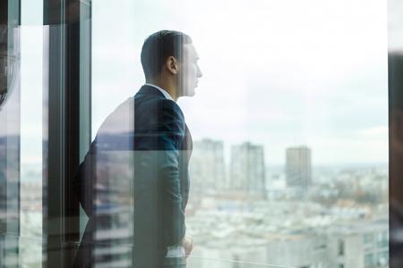 ビジネスマンのガラスドアを通して見たオフィスのバルコニーの外を見るします。