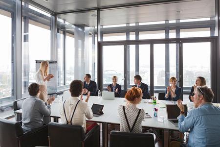 Gente di affari che applaude le mani dopo la riuscita riunione nell'ufficio moderno.