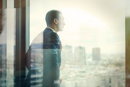 L'uomo d'affari guardando fuori attraverso il balcone dell'ufficio visto attraverso le porte di vetro. Post trasformati con filtro vintage.