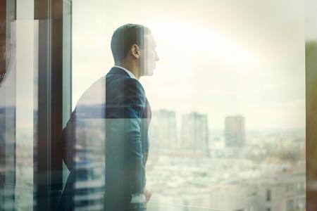 Zakenman kijkt uit via het kantoor balkon gezien door glazen deuren. Bericht bewerkt met vintage filter.