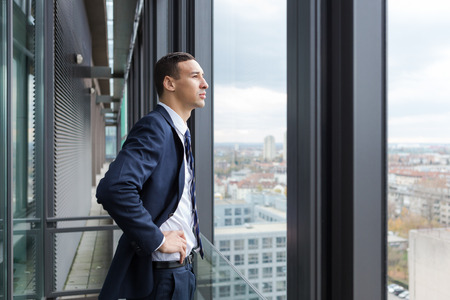 man looking out: Business man looking out through the office balcony. Stock Photo