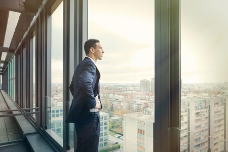 personas mirando: hombre de negocios que mira hacia fuera a través del balcón de la oficina. Publicar procesada con el filtro de la vendimia.