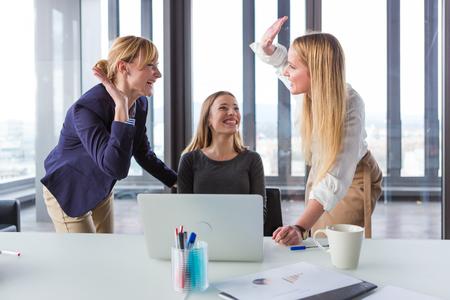 Tre donne d'affari in ufficio moderno celebra buoni risultati del progetto.