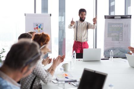 Hipster uomo d'affari che presenta il progetto in ufficio moderno.