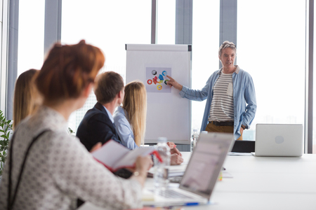 brain storming: Business man pointing at charts on flipchart during the meeting in modern office. Stock Photo