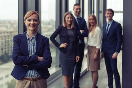 Office women: Corporate portrait of young business woman with her colleagues in background. Post processed with vintage film and sun filter.