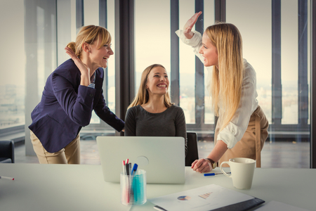 brain storming: Three business women in modern office celebrating good project results. Post processed with vintage film filter. Stock Photo
