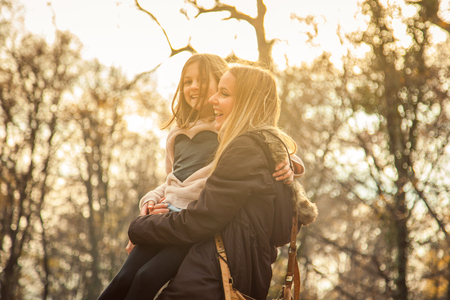 cheerfull: Cheerfull mother holdes daughter in park on an autumn day. Stock Photo