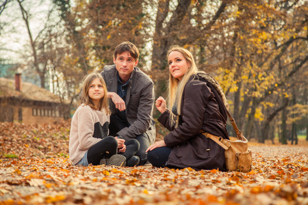 to kneel: Family of three kneel in park on an autumn day. Foto de archivo