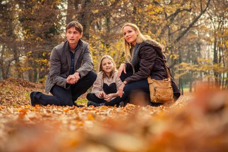 to kneel: Familia alegre de tres arrodillarse en el parque suelo cubierto de hojas en un d�a de oto�o.