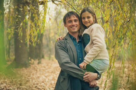 tree canopy: Father holds daughter in hands under tree canopy.
