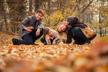 to kneel: Cheerful family of three kneel on park ground covered with leaves on an autumn day.