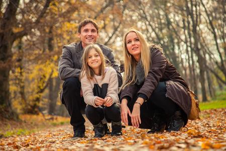 arrodillarse: Zagreb, Croacia - 15 de noviembre de 2015: Familia de tres arrodillarse en el parque en un día de otoño.