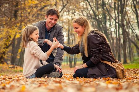 arrodillarse: Familia alegre de tres arrodillarse en el parque suelo cubierto de hojas en un día de otoño.