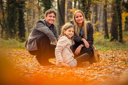 to kneel: ZAGREB, CROATIA - 15 NOVEMBER 2015: Cheerful family of three kneel on park ground covered with leaves on an autumn day.