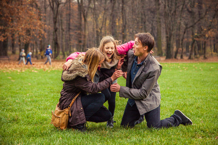 sneaks: Family of three in park. Daughter sneaks on parents.