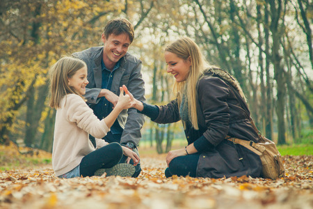 arrodillarse: Familia de tres arrodillarse en el parque en un día de otoño. Foto de archivo