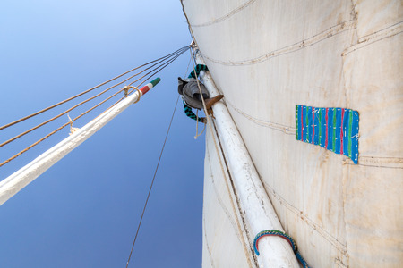 traditional climbing: Man climbing mast on felucca, traditional wooden sailboat on Nile, Egypt.