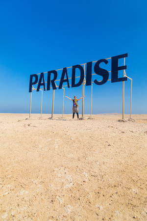 spreading arms: Tourist spreading arms under the Paradise sign.