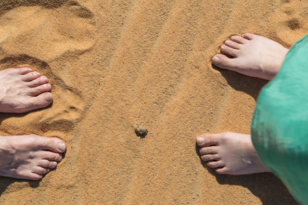 bare feet: Male and female bare feet in the sand.