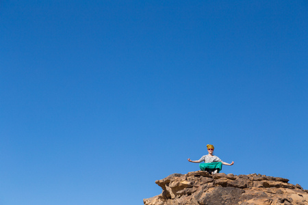spreading arms: Tourist with turban and sunglasses spreading arms on big rock in desert, Egypt.