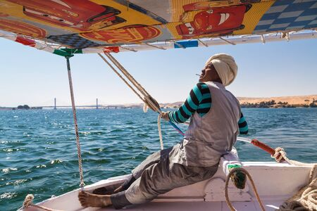 sailing crew: EGYPT -  FEBRUARY 8, 2016: Nubian felucca sailing crew member holding ropes on trip on the Nile.