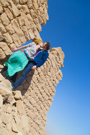 africa kiss: Tourist couple kissing in front of ruined stone house in desert, Egypt.