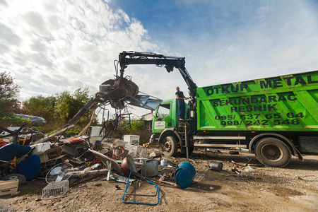 recoger: ZAGREB, CROATIA - OCTOBER 14, 2013: Truck driver using crane to collect garbage from recycling yard. Editorial
