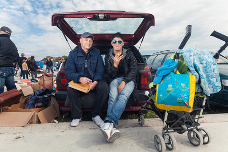 car trunk: ZAGREB, CROATIA - OCTOBER 20, 2013: Young Roma man sitting at the car trunk with salesman at Zagrebs flea market Hrelic.