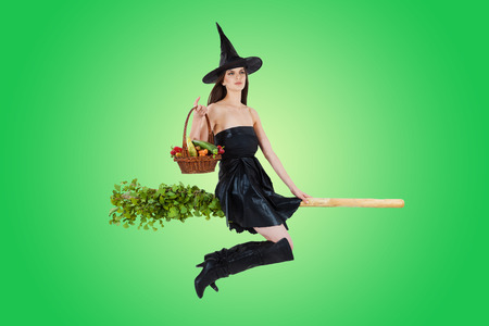 Young woman dressed as a witch carrying vegetable basket and riding a broom. Radial green background. photo