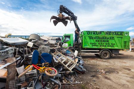 recoger: Zagreb, Croacia - OCTUBRE 14 de, 2013: Conductor de camión utilizando la grúa para recoger la basura de reciclaje patio.